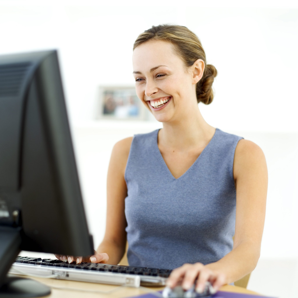 Young Woman Sitting in Front of a Computer and Laughing --- Image by © Royalty-Free/Corbis